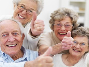 Group of older people showing thumbs up